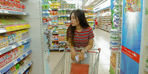 Woman leaning on handle of grocery cart with cell phone in hand, looking at items on shelves in grocery store.